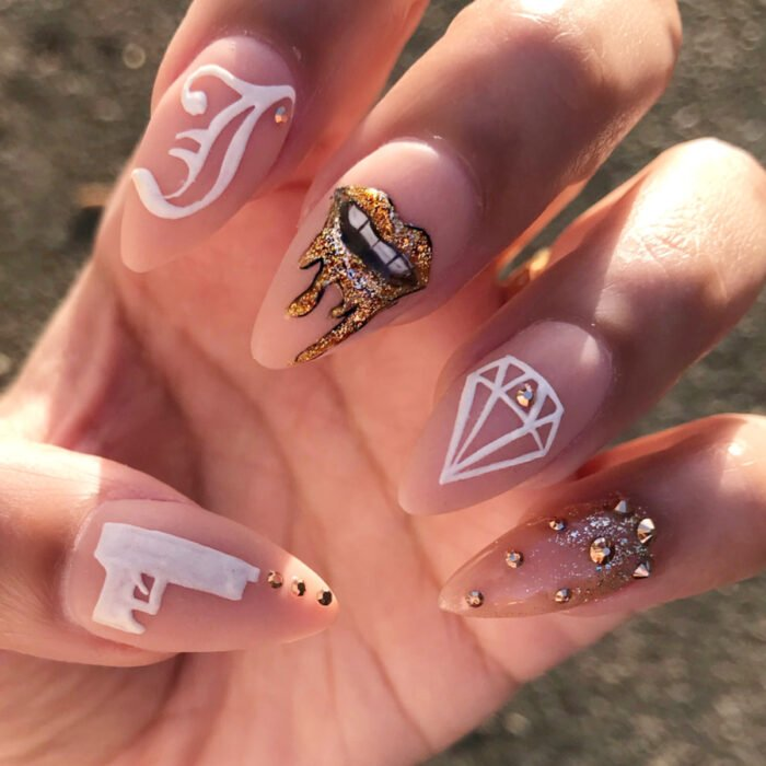 Hands with long almond-shaped nails painted with nude nail polish, with lettering design, lips with gold diamond, diamond and studs