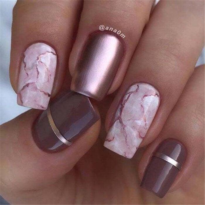 Chica con las uñas en un diseño metálico de color rosa con diseños en marmol