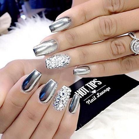 Chica con las uñas en un diseño metálico de color plateado con toques de piedras blancas