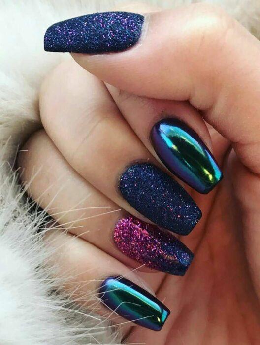 Chica con las uñas en un diseño metálico de color azul con toques rosas y morados