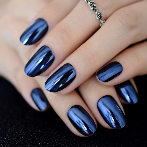 Girl with nails in a metallic navy blue design
