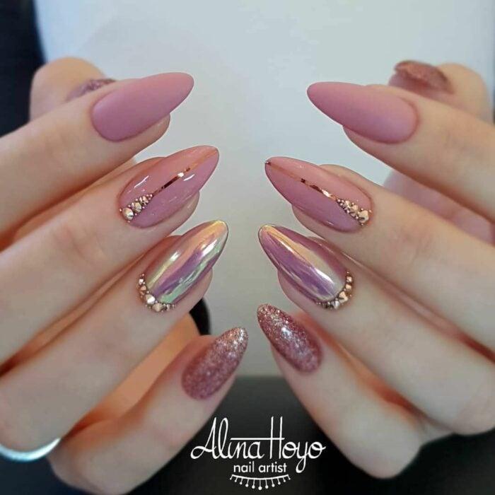 Chica con las uñas en un diseño metálico de color rosa mate y rosa brillante