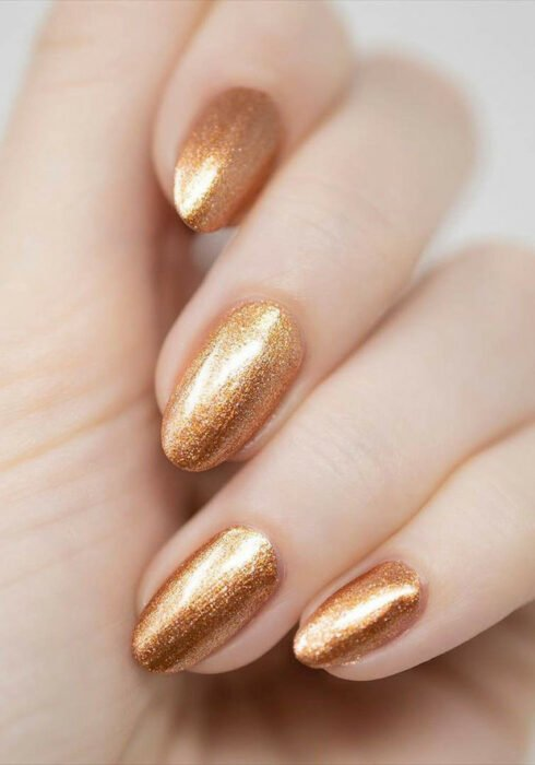 Girl with nails in a metallic copper-colored design