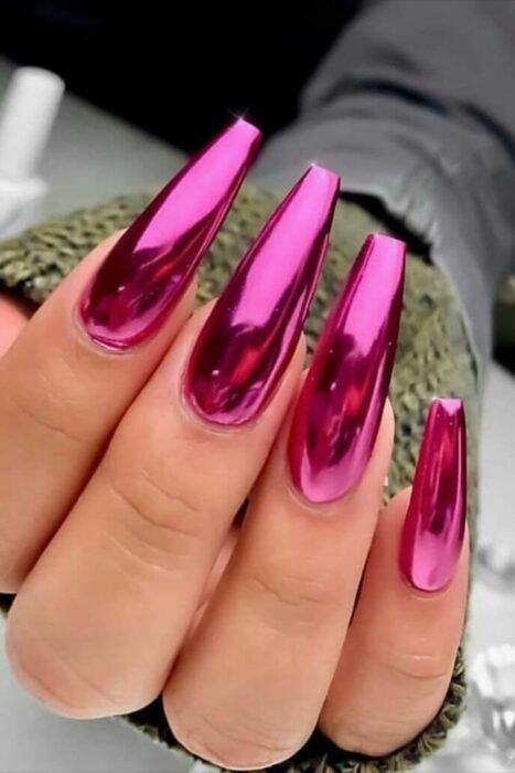 Girl with nails in a fuccia pink metallic design