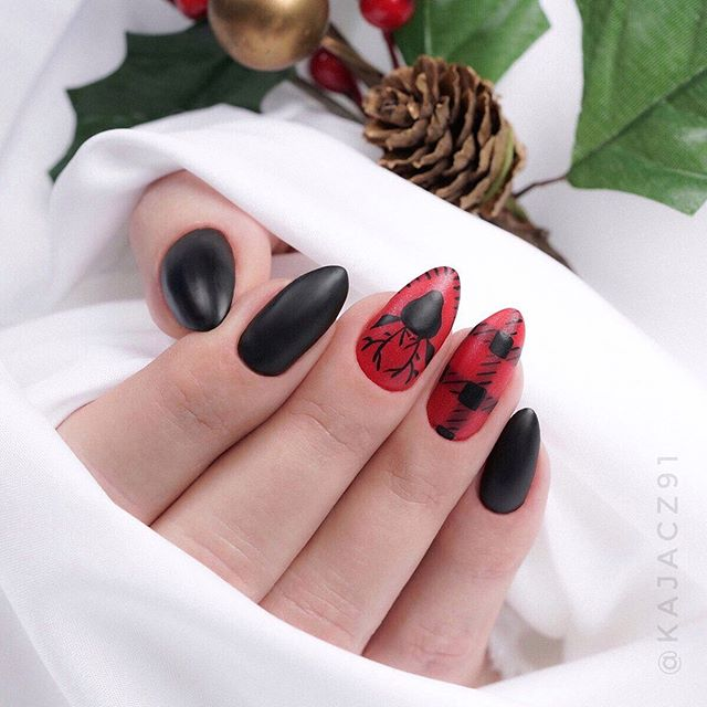 Nails painted in red, black base color with Christmas reindeer decoration; Christmas manicure designs
