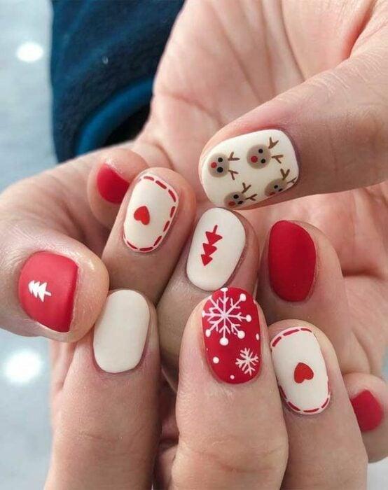Uñas pintadas en tonos blanco y rojo con difuras navideñas de copos de nieve; diseños manicuras navideñas