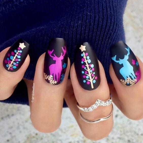 Uñas pintadas con base en tono negro y figuras navideñas en colores fluorescentes; diseños manicuras navideñas