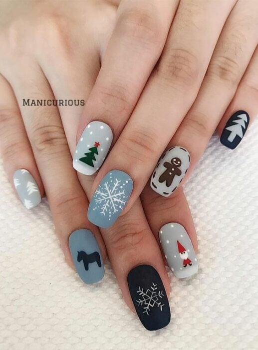 Uñas en color base gris y azul decoradas con motivos navideños; diseños manicuras navideñas