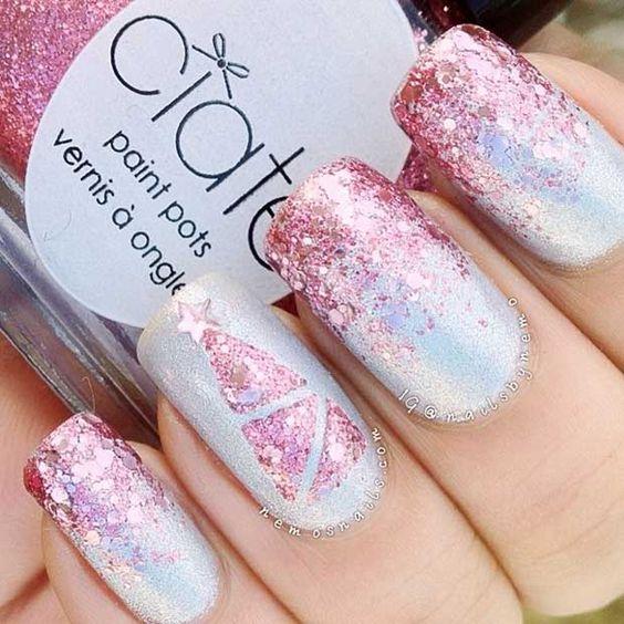 Uñas en tono base plata con decoraciones en rosa glitter; diseños manicuras navideñas