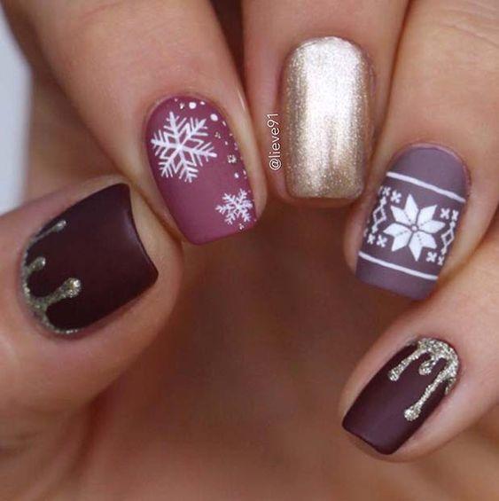 Uñas en tonos morados con decoración de copos navideños en blanco; diseños manicuras navideñas