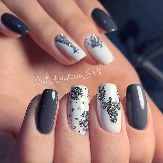 Uñas pintadas en tonos base gris, blanco con diseño de renos navideños en plata; diseños manicuras navideñas