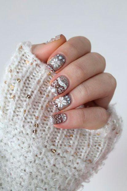 Uñas en tonos base neutros con decoración inspirada en suéteres; diseños manicuras navideñas