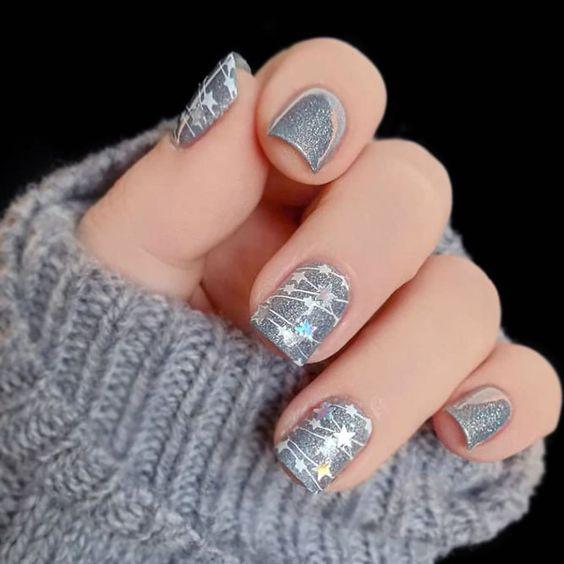 Uñas en color base plata con destellos blancos en forma de estrella; diseños manicuras navideñas