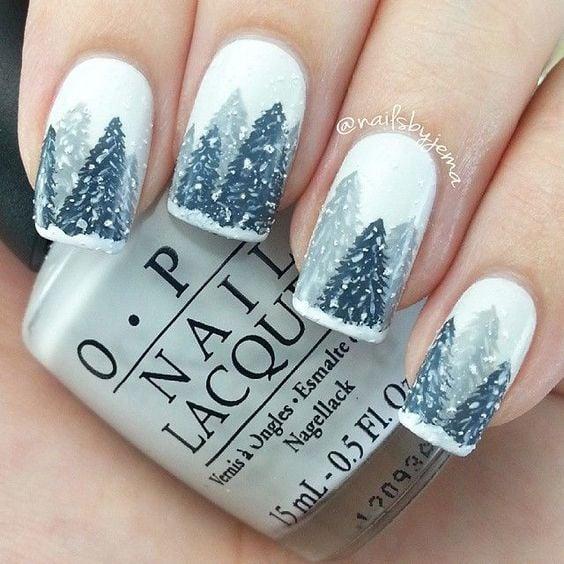 Uñas pintadas con tono base en blanco y dibujos de pinos navideños en grises; diseños manicuras navideñas
