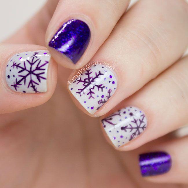Uñas pintadas en tonos base blanco, morado con decoración de copos navideños; diseños manicuras navideñas