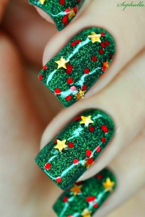 Nails painted in green as a base with glitters and yellow stars; Christmas manicure designs