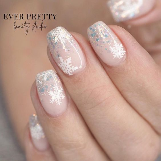 Nails in pale pink base tone with white and gray snowflake decoration; Christmas manicure designs