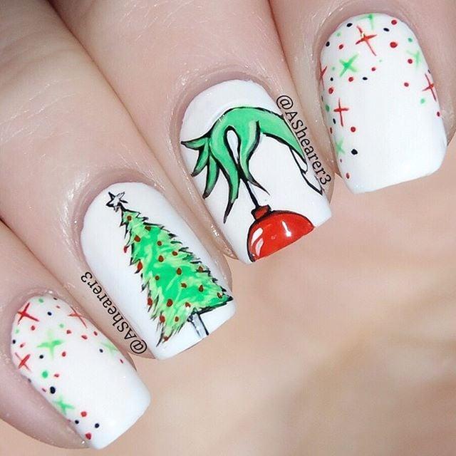 Uñas pintadas en tono base blanco con decoración de esferas de colores y alusivos a El Grinch; diseños manicuras navideñas