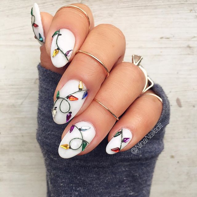 Nails painted in white with colored Christmas lights design; Christmas manicure designs