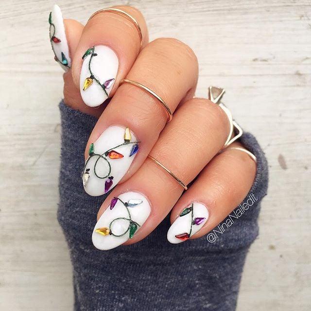 Uñas pintadas en color blanco con diseño de luces navideñas de colores; diseños manicuras navideñas
