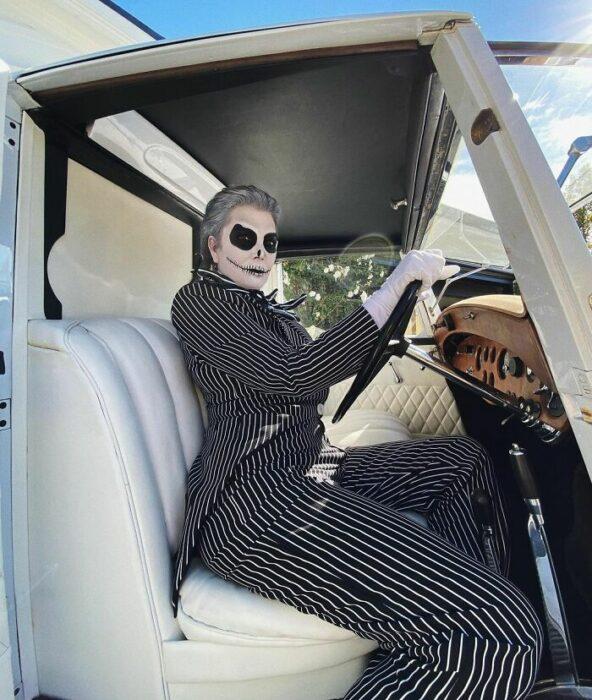Kris Jenner posando en un automóvil blanco al volante disfrazada como Jack  skellington