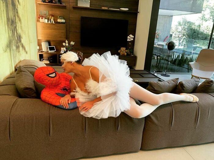 Chrissy Teigen y John Legend acostado en un sillón disfrazados como Spiderman y el cisne blanco