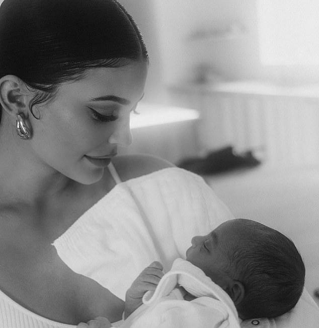Kylie Jenner sosteniendo a su sobrino Psalm en brazos mientras lo mira fijamente