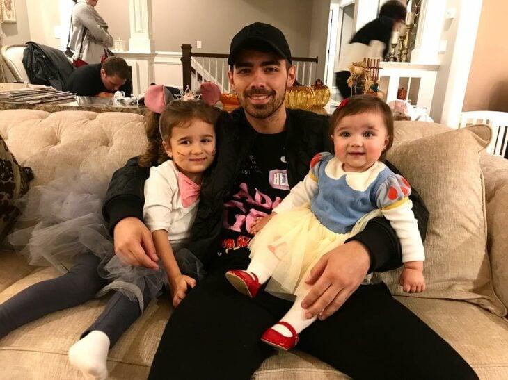 Joe Jonas sentado junto a sus sobrinas mientras están jugando
