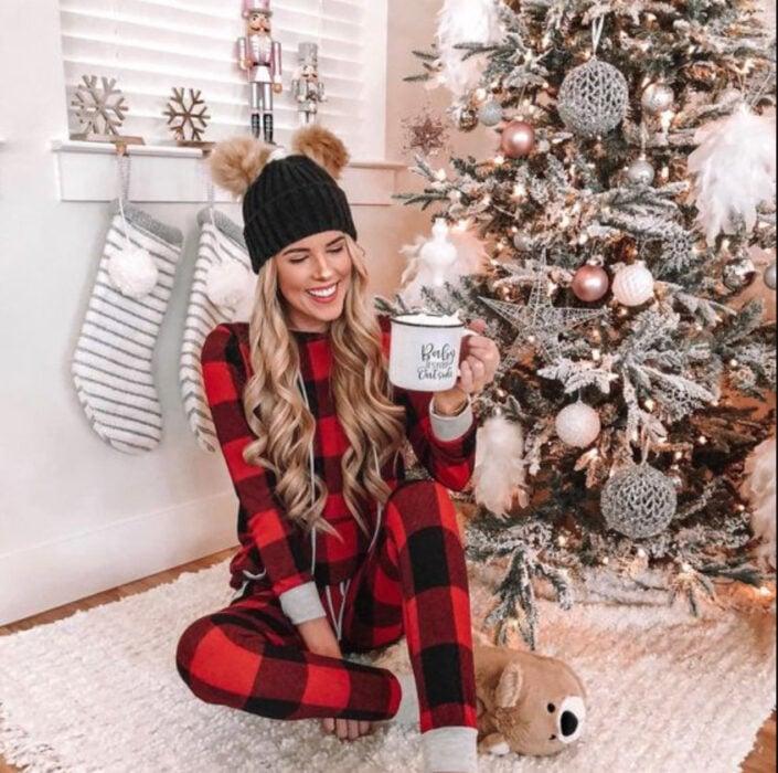 Chica usando pijama de navidad, sentada sobre el suelo, delante del árbol de navidad bebiendo una taza de chocolate caliente