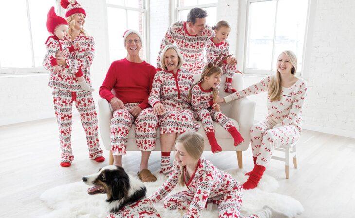 Familia completa en la sala, usando la misma pijama de navidad riendo y disfrutando