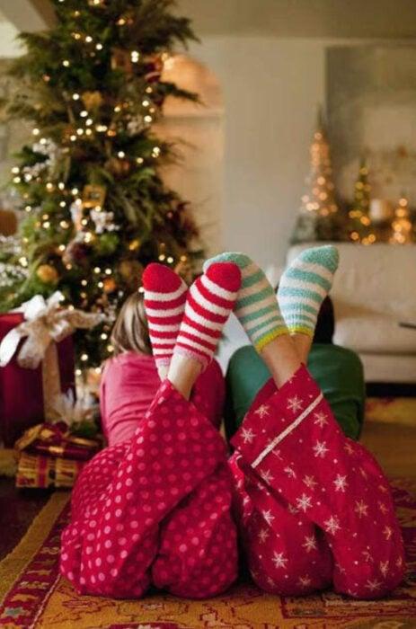 Dos pares de pies usando pijamas y calcetines de navidad con el árbol de navidad de fondo