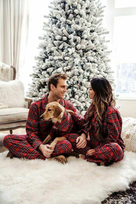Pareja sentados sobre el suelo, usando la misma pijama posando delante de su árbol de navidad y acompañados de su perro