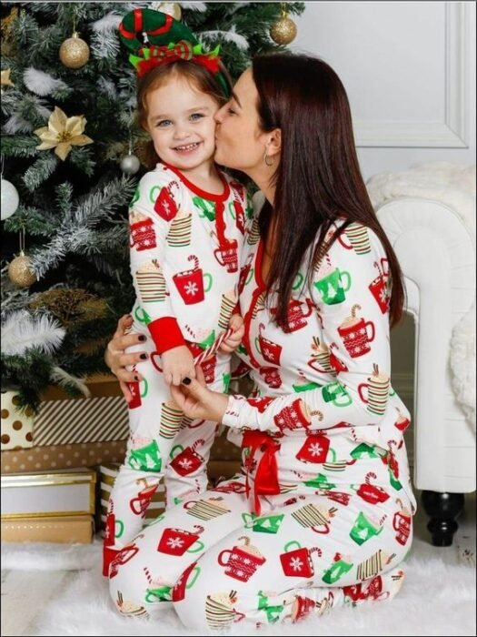Mujer y niña usando la misma pijama, la mujer le besa la mejilla a la nula y con el árbol de navidad detrás de ambas