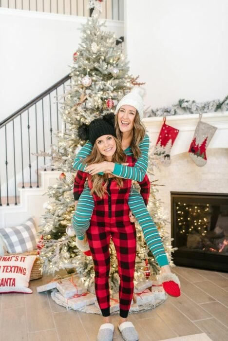 Amigas usando pijamas de navidad, posando delante del árbol mientras se divierten