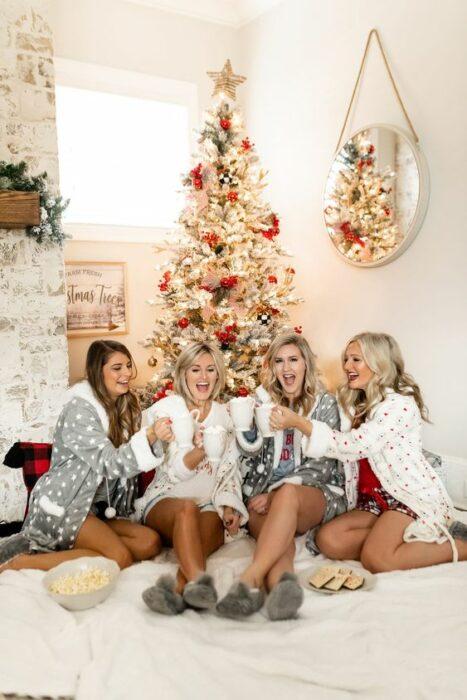 Grupo de amigas, usando batas de navidad, sentadas delante del árbol de navidad mientras pasan un buen rato juntas
