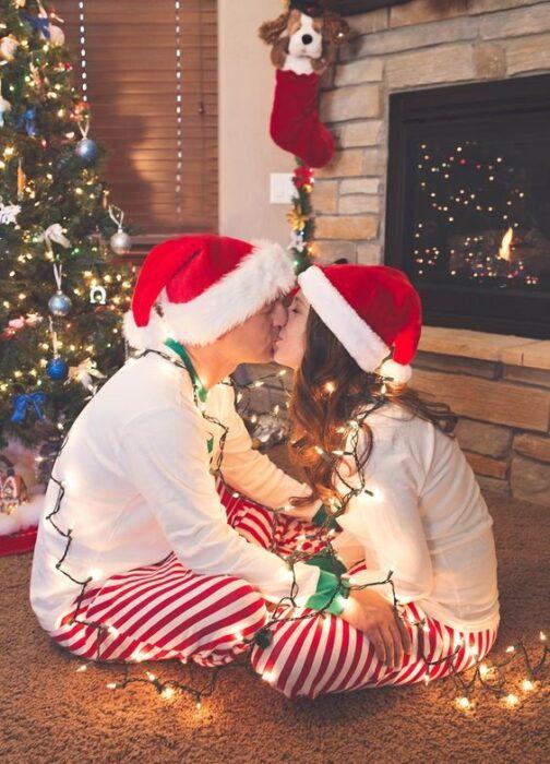 Pareja sentada de frente con el árbol de navidad detrás de ellos, besándose rodeados con luces navideñas
