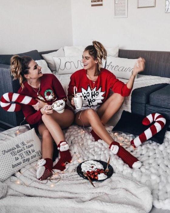 Par de amigas, sentadas en el suelo, usando pijamas de navidad mientras ríen y beben chocolate caliente