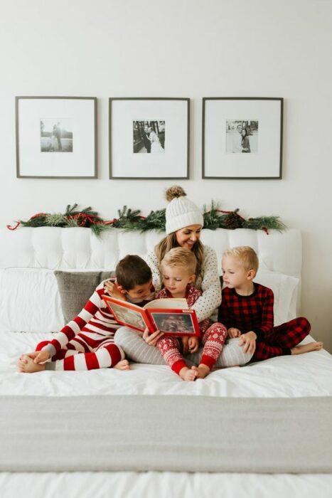 Chica con tres niños, todos sentados sobre la cama usando pijamas de navidad, mientras leen un cuento