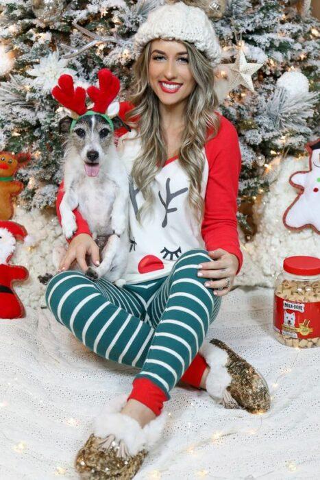 Chica usando pijama de navidad, sentada delante del árbol navideño, acompañada de su perro que usa una diadema de reno