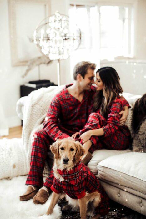 Hombre, mujer y perro con pijamas rojas de cuadros sentados en un sillón grande blanco