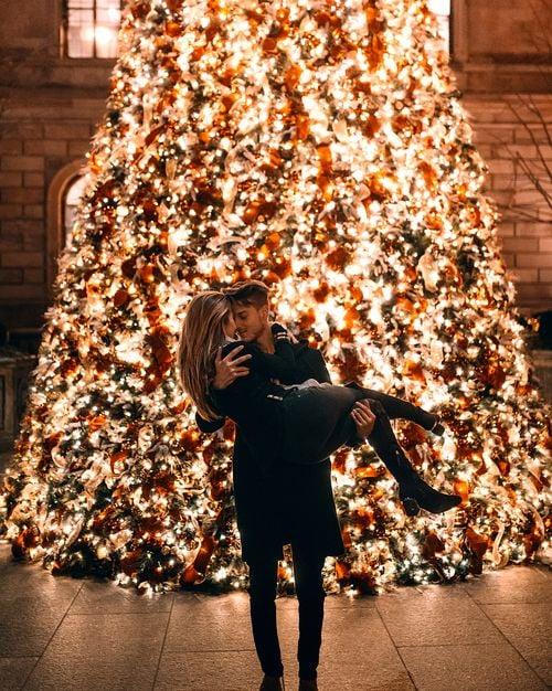 Chico alzando a chica rubia de cabello largo frente a árbol de navidad gigantes con luces encendidas