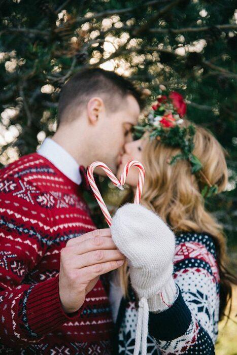 Hombre con camisa blanca y suéter rojo y mujer rubia de cabello largo con una corona de flores en la cabeza unen sus manos al centro para formar un corazón con dos bastones de caramelo
