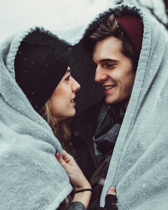 Mujer rubia con gorrito negro y hombre de cabello castaño con gorrito guinda se cubren con una manta color azul formando un corazón