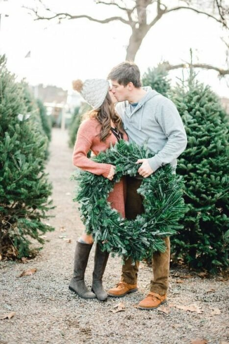 Mujer castaña de cabello ondulada con gorro gris y suéter naranja besa a hombre con suéter gris mientras ambos sostienen corona navideña hecha de ramas de pino