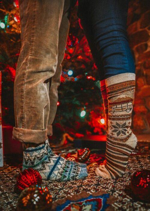 Piernas de hombre y de mujer con calcetas gruesas navideñas