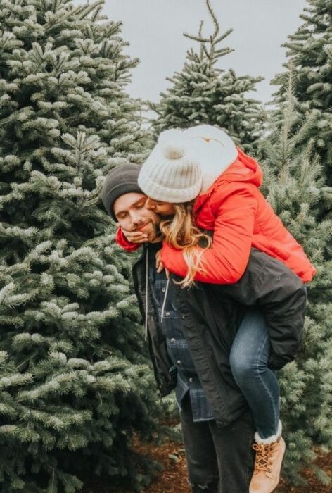 Hombre con gorro gris y chamarra negra carga en su espalda a chica rubia con gorro blanco y chamarra roja con pinos navideños de fondo