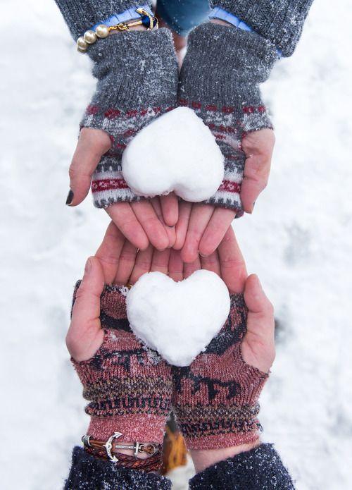 Manos de una pareja unido en medio de foro ambas con guantes de navideños con dos corazones de nieve