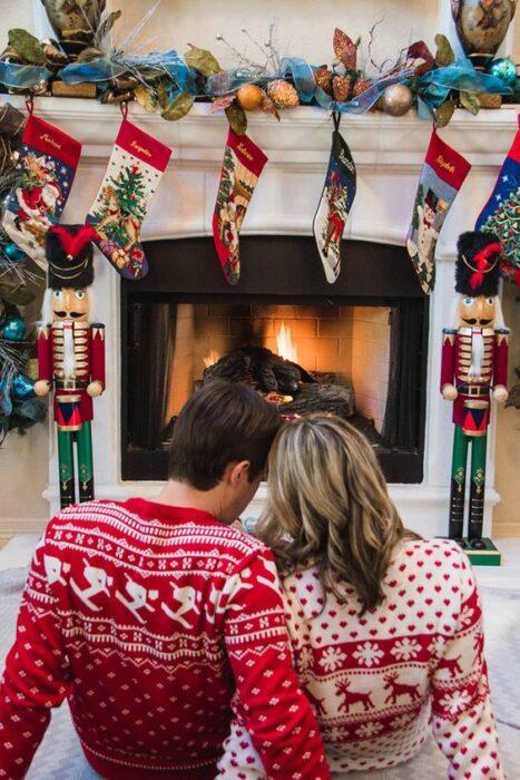 Pareja con suéter rojos navideños sentados frente a chimenea encendidablanca con botas de colores colgadas