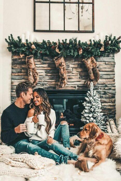 Pareja sentada junto a chimenea apagada con botas cafés colgadas y un pinito navideño ambos con tazas de café en las mano y un perro café acostado en la alfombra
