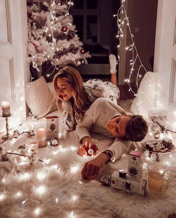 Pareja con pijamas blancas acostados y riendo en una alfombra blanca con luces navideñas en el piso y un árbol de navidad en el fondo
